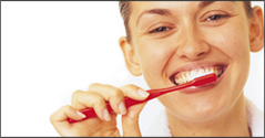 Woman brushing teeth with Invisalign clear braces